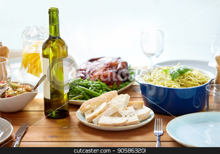bottle of wine and food on served wooden table stock photo, food, thanksgiving day and eating concept - bottle of wine with bread, pasta and roast chicken on served wooden table by Syda Productions