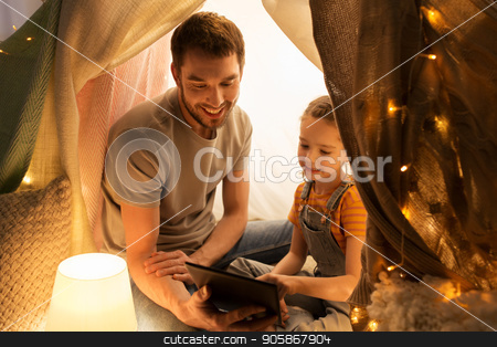 family with tablet pc in kids tent at home stock photo, family, hygge and technology concept - happy father and little daughter with tablet pc computer in kids tent at night at home by Syda Productions