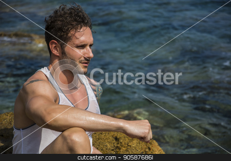 Handsome muscular man on the beach sitting on rocks stock photo, Handsome muscular man on the beach sitting on rocks, looking at camera by Stefano Cavoretto