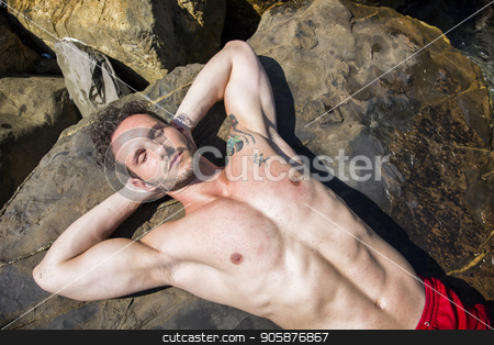 Handsome muscular man on the beach laying on rocks stock photo, Handsome muscular shirtless man on the beach lying on rocks, looking up to the sky by Stefano Cavoretto