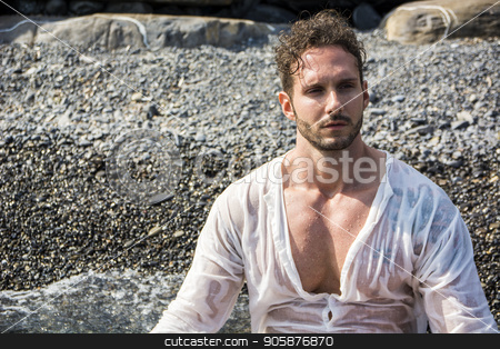 Handsome muscular man on the beach laying on gravel stock photo, Handsome muscular man on the beach lying on gravel, wearing wet white shirt by Stefano Cavoretto