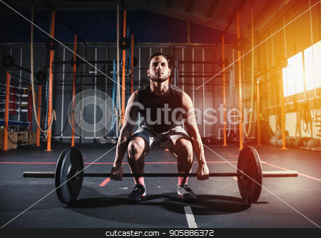 Athletic man works out at the gym with a barbell stock photo, Determined athletic man works out at the gym with a barbell by Federico Caputo