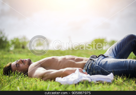 Shirtless fit male model relaxing lying on the grass stock photo, Good looking, shirtless fit male model relaxing lying on the grass, shot from above by Stefano Cavoretto
