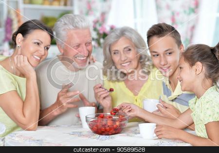 Big happy family eating fresh strawberries at kitchen stock photo, Portrait of big happy family eating fresh strawberries at kitchen by Ruslan Huzau