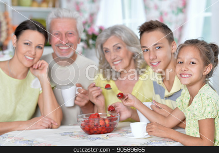 Big happy family eating fresh strawberries at kitchen stock photo, Portrait of big happy family eating fresh strawberries at kitchen by Ruslan Huzau
