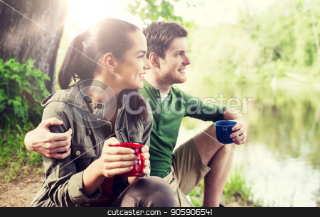 happy couple with cups drinking in nature stock photo, travel, tourism, hike, camping and people concept - happy couple with cups drinking tea in nature on river bank by Syda Productions