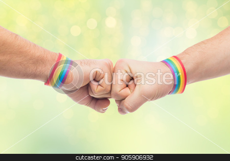 hands with gay pride wristbands make fist bump stock photo, lgbt, same-sex love and homosexual relationships concept - close up of male couple hands with gay pride rainbow awareness wristbands making fist bump gesture over green lights background by Syda Productions