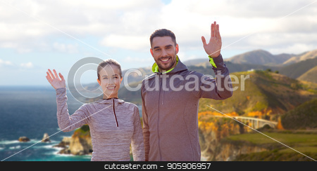 smiling couple in sport clothes waving hand stock photo, fitness, sport, and healthy lifestyle concept - smiling couple waving hand over bixby creek bridge on big sur coast of california background by Syda Productions