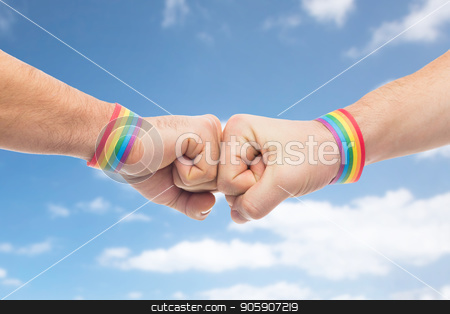 hands with gay pride wristbands make fist bump stock photo, lgbt, same-sex love and homosexual relationships concept - close up of male couple hands with gay pride rainbow awareness wristbands making fist bump gesture over blue sky and clouds background by Syda Productions