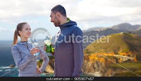couple of sportsmen with water over big sur coast stock photo, fitness, sport and people concept - smiling couple with bottles of water over bixby creek bridge on big sur coast of california background by Syda Productions