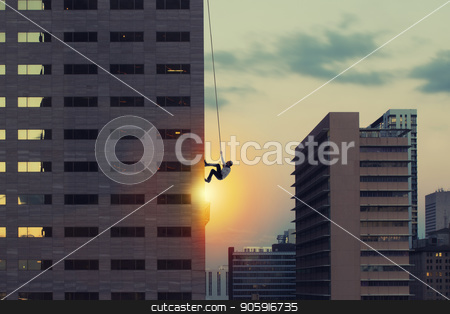 Businessman climb a skyscraper. Achievement business goal and difficult career concept stock photo, Businessman climb a skyscraper with a rope. Achievement business goal and difficult career concept by Federico Caputo