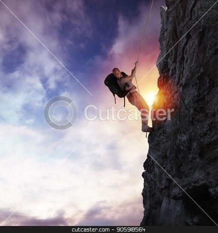 Man climbs a high danger mountain with a rope during sunset stock photo, Explorer man climbs a high danger mountain with a rope during sunset by Federico Caputo