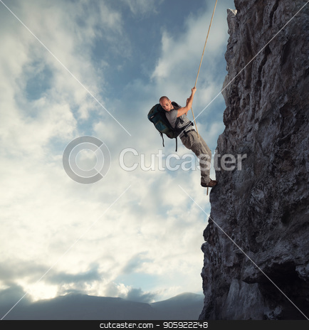 Man climbs a high danger mountain with a rope stock photo, Explorer man climbs a high danger mountain with a rope by Federico Caputo
