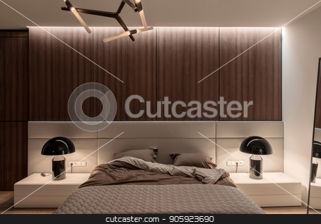 Stylish modern bedroom stock photo, Bedroom in a modern style with white and wooden walls, parquet on a floor and luminous fancy lamps. There is a bed with a brown linens and a gray plaid, mirror, night stands. Horizontal. by bezikus