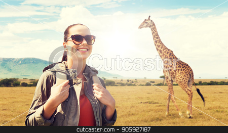 happy woman with backpack traveling in africa stock photo, travel, tourism and people concept - happy young woman in sunglasses with backpack over african savannah and giraffe background by Syda Productions