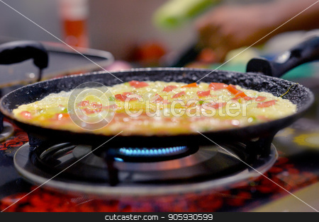 preparing meal on stove  stock photo, fried eggs with vegetables preparing in pan  on stove by Ruslan Huzau