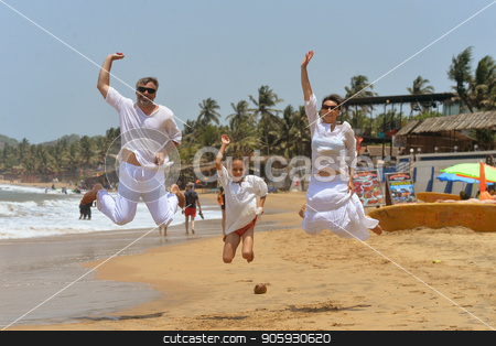 happy family hugging stock photo, Portrait of happy family jumping on sandy beach by Ruslan Huzau