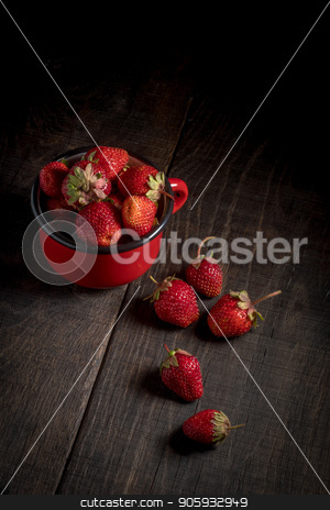 Strawberries in an iron mug on a wooden table. stock photo, Dark photo of a strawberry. Strawberries on a wooden background. Healthy food. Organic food. Fruit on a wooden table. by YuriiZ