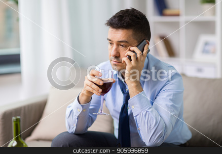 drunk man with alcohol calling on smartphone stock photo, alcoholism, alcohol addiction and people concept - male alcoholic drinking wine and calling on smartphone at home by Syda Productions
