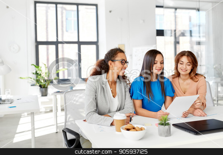 businesswomen discussing papers at office stock photo, business, teamwork and people concept - female team or businesswomen discussing papers at office by Syda Productions
