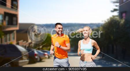 smiling couple running stock photo, fitness, sport and healthy lifestyle concept - smiling couple with heart-rate watch running over san francisco city background by Syda Productions