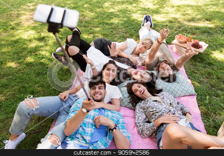friends taking picture by selfie stick at picnic stock photo, friendship, leisure and technology concept - group of happy smiling friends taking picture by selfie stick chilling on picnic blanket at summer park by Syda Productions