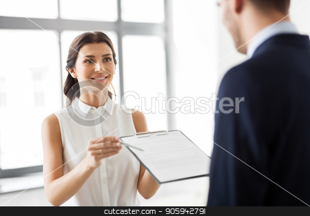 realtor showing contract document to customer stock photo, real estate business, sale and people concept - female realtor with clipboard showing contract document to customers at new office room by Syda Productions