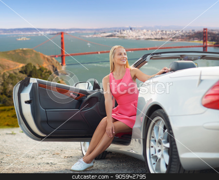 woman in convertible car over golden gate bridge stock photo, travel, road trip and people concept - happy young woman posing in convertible car over golden gate bridge in san francisco bay background by Syda Productions