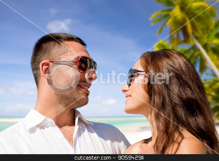 happy couple in sunglasses over tropical beach stock photo, travel, tourism and summer vacation concept - happy smiling couple in sunglasses over tropical beach background in french polynesia by Syda Productions