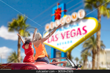 friends driving in convertible car at las vegas stock photo, summer holidays, road trip and travel concept - happy friends driving in convertible car and waving hands over welcome to fabulous las vegas sign background by Syda Productions