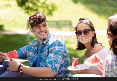happy friends eating watermelon at summer picnic stock photo, friendship, leisure and summer concept - group of happy friends eating watermelon at picnic in park by Syda Productions