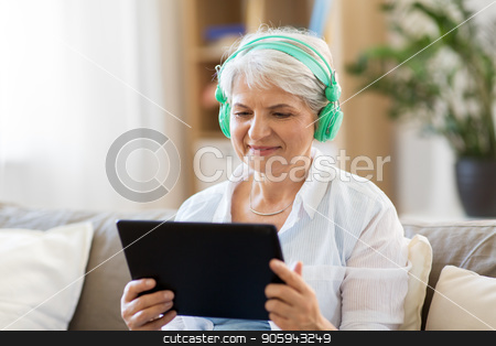 senior woman in headphones listening to music stock photo, technology, people and lifestyle concept - happy senior woman in headphones and tablet pc computer listening to music at home by Syda Productions