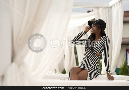 Sexy afican american girl posing for camera wearing stripped long dress and big black hat. Girl sitting on a white bench. White fabrics on the background. stock photo, Sexy afican american girl posing for camera wearing stripped long dress and big black hat. Girl sitting on a white bench. White fabrics on the background. by Andrii Kobryn