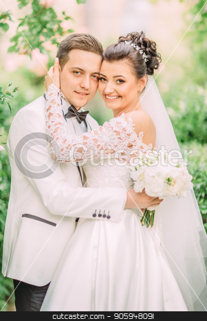 Side portrait of the hugging newlyweds holding the wedding bouquet. stock photo, Side portrait of the hugging newlyweds holding the wedding bouquet by Andrii Kobryn