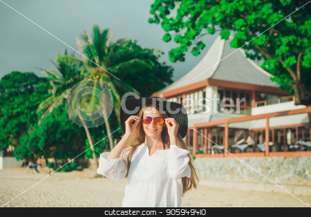 handsome girl with glasses and hat on the beach background. Portrait of a woman in white clothes and balck hat stock photo, handsome girl with glasses and hat on the beach background. Portrait of a woman in white clothes and balck hat by aaalll3110