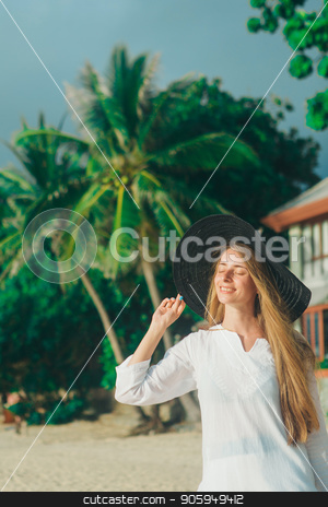 handsome girl in hat on the beach background. Portrait of a woman in white clothes and balck hat stock photo, handsome girl in hat on the beach background. Portrait of a woman in white clothes and balck hat by aaalll3110