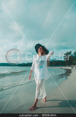 handsome girl in hat on the beach background. Portrait of a woman in white clothes and balck hat on the sea
