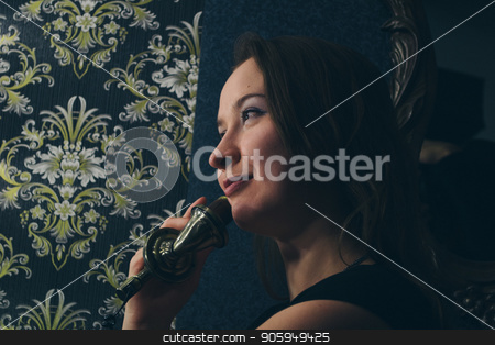 portrait of a female face closeup. The girl smiles and holds up the old phone to the ear on the background of walls with murals stock photo, portrait of a female face closeup. The girl smiles and holds up the old phone to the ear on the background of walls with murals by aaalll3110