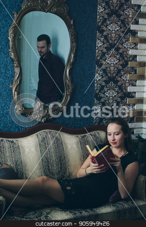 Girl in black dress reading a book on the couch, the mirror reflects the man stock photo, Girl in black dress reading a book on the couch, the mirror reflects the man by aaalll3110