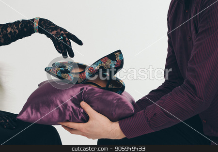 The shoes in jewels on a purple pillow. A man brings shoes to a girl, she points her finger at them in a black glove. stock photo, The shoes in jewels on a purple pillow. A man brings shoes to a girl, she points her finger at them in a black glove. by aaalll3110