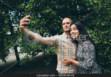 A guy with a girl taking selfies on a green foliage background stock photo, A guy with a girl taking selfies on a green foliage background by aaalll3110