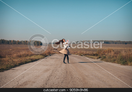 A woman with a child in his arms on the road in the middle of a wasteland stock photo, A woman with a child in his arms on the road in the middle of a wasteland by aaalll3110