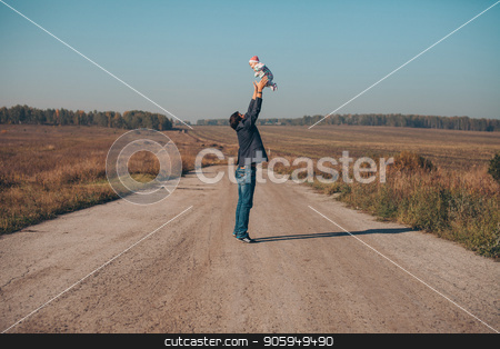 A man with a child in his arms on the road in the middle of a wasteland stock photo, A man with a child in his arms on the road in the middle of a wasteland by aaalll3110