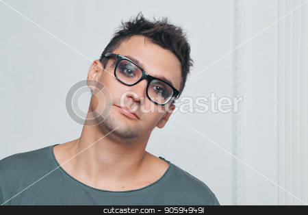 A man in a gray t-shirt with brightly colored eyes looks into the camera. Portrait of a brunette with makeup and glasses stock photo, A man in a gray t-shirt with brightly colored eyes looks into the camera. Portrait of a brunette with makeup and glasses by aaalll3110
