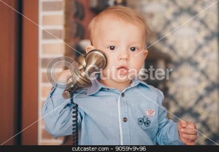 A little blond boy in a blue shirt is calling on the phone stock photo, A little blond boy in a blue shirt is calling on the phone by aaalll3110