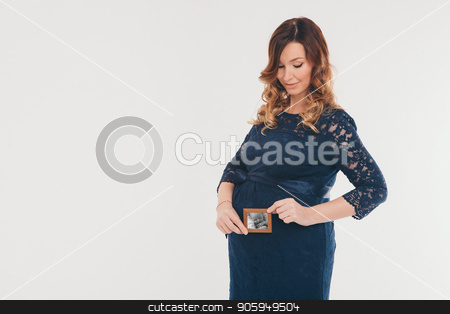 a pregnant woman holding a photo of her unborn child. Isolated photo on white background stock photo, a pregnant woman holding a photo of her unborn child. Isolated photo on white background by aaalll3110