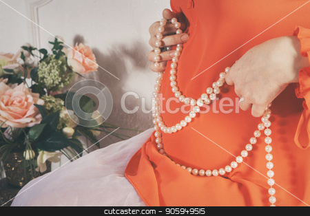 a pregnant woman in an orange dress holding a necklace of pearls on a background of stomach stock photo, a pregnant woman in an orange dress holding a necklace of pearls on a background of stomach by aaalll3110