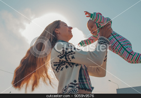 A long-haired woman in a knitted sweater holds a little child in a color striped suit against the blue sky and the sun. Girl with long blonde hair circling her newborn baby stock photo, A long-haired woman in a knitted sweater holds a little child in a color striped suit against the blue sky and the sun. Girl with long blonde hair circling her newborn baby by aaalll3110