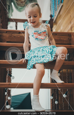 a little blond girl in a white and blue dress in polka dots and light socks descends a wooden ladder crawling stock photo, a little blond girl in a white and blue dress in polka dots and light socks descends a wooden ladder crawling by aaalll3110