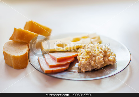 Fresh bread, meat slices, Maasdam cheese, wheat porridge on a transparent glass plate on a white table stock photo, Fresh bread, meat slices, Maasdam cheese, wheat porridge on a transparent glass plate on a white table by aaalll3110